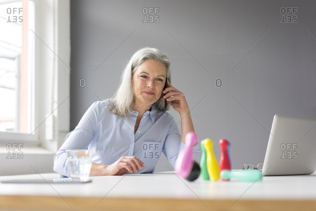 Mature businesswoman on the phone playing with pins on desk in office
