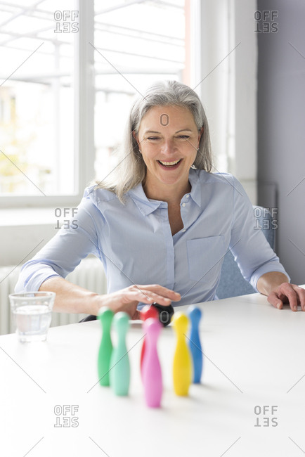 Laughing mature businesswoman playing with pins on desk in office