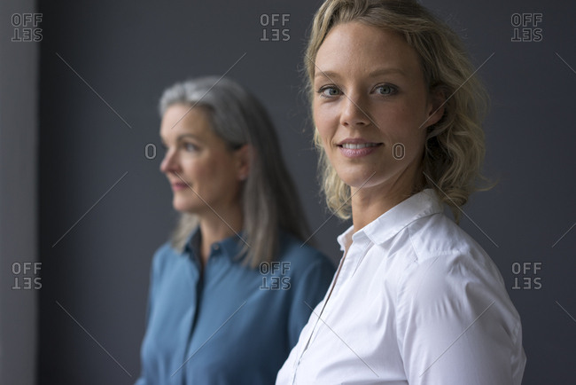 Portrait of smiling young businesswoman with mature businesswoman in background