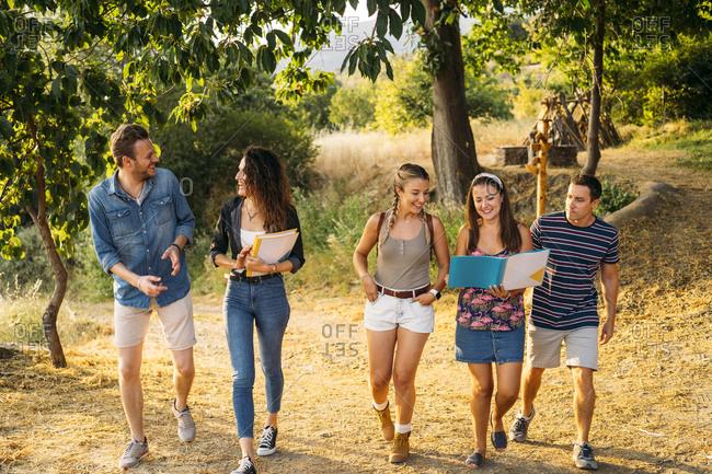 Happy friends on a field trip with folders in rural landscape
