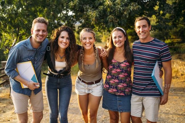 Portrait of happy friends on a field trip with folders in rural landscape