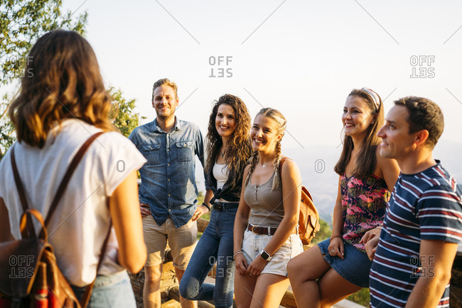 Group of friends looking at woman leading a tour