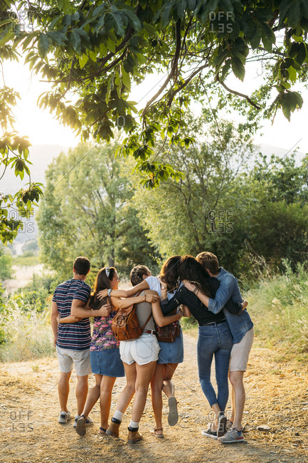 Rear view of friends embracing and walking on a rural path