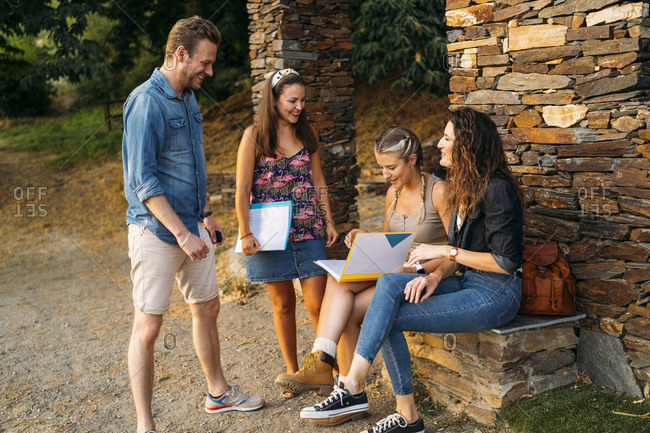 Happy friends with folders at a stone house in the countryside
