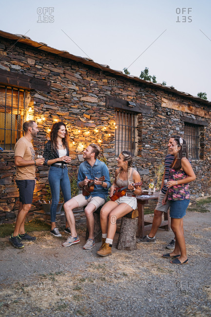 Group of friends playing ukulele outdoors at a stone house at dusk