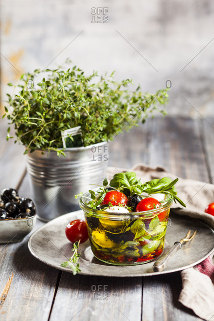 Potted thyme and jar of fresh Caprese salad preserved in olive oil