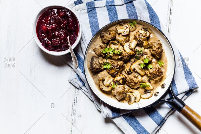 Frying pan with Swedish kottbullar meatballs in mushroom gravy and bowl of mashed cranberries