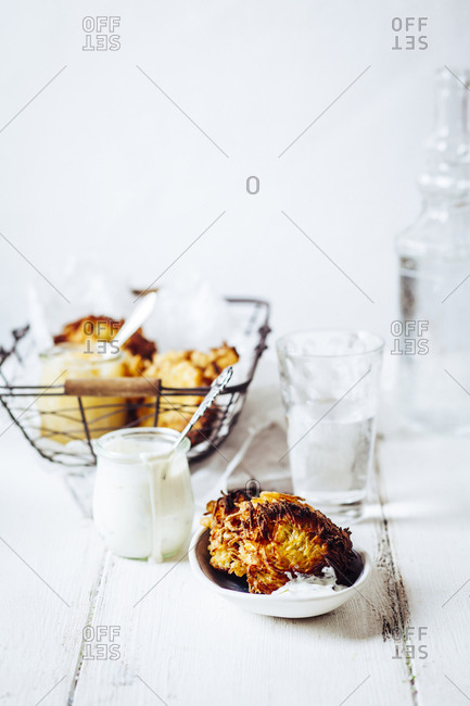 Jar of sour sauce and bowl of crunchy Jewish latkes