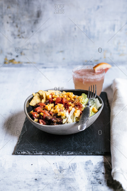 Bowl of nachos with- chili con carne- rice- lettuce- cheese- tomatoes and glass of refreshing paloma cocktail
