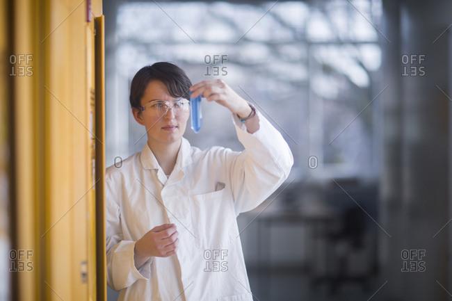 Female chemist at work examining a liquid
