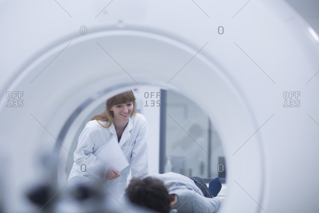 Patient in hospital during CT examination- female radiologist smiling
