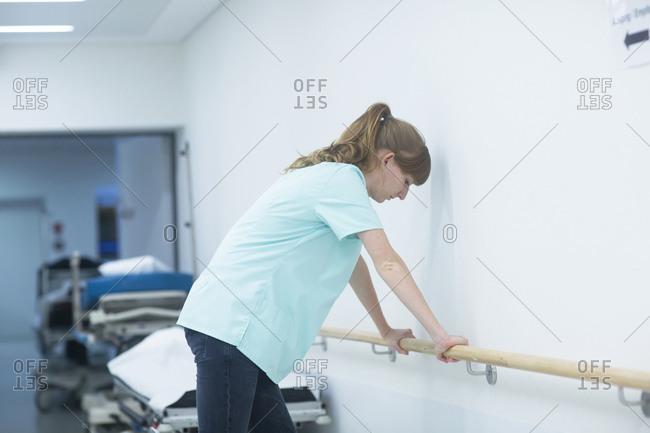 Female radiologist resting on railing in a hospital