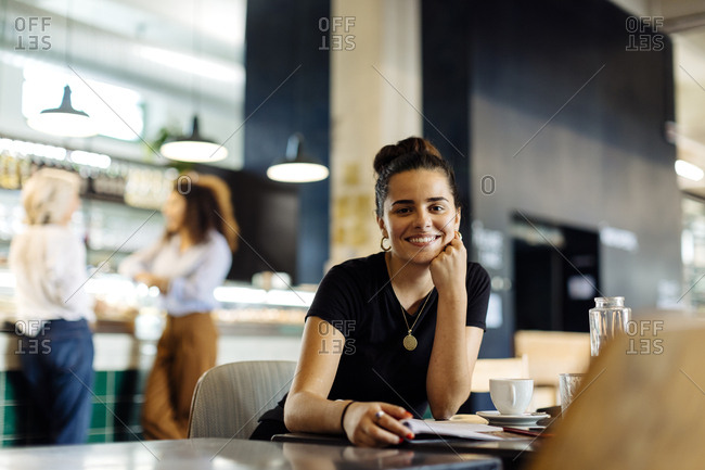 Young woman sitting in bistro- reading magazine