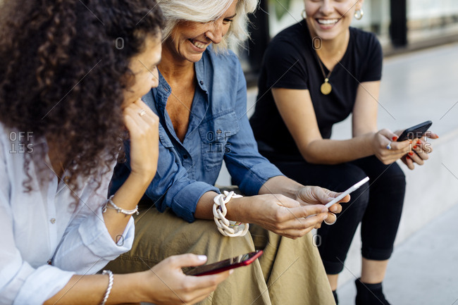 Three women sitting on steps in a row- using smartphones