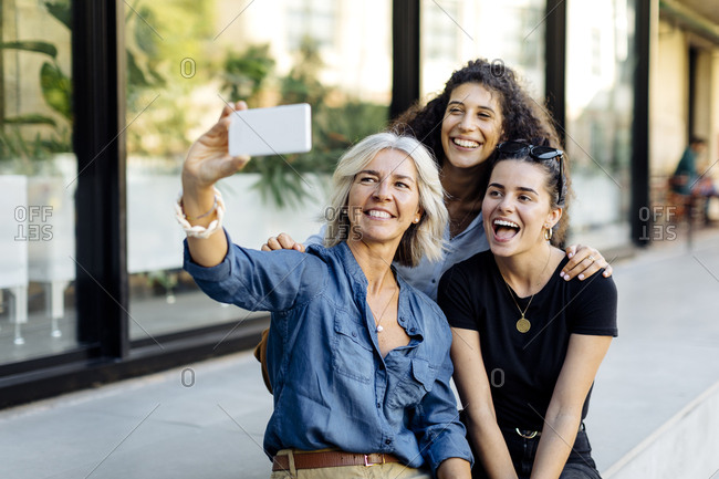Three laughing women taking selfie in the city