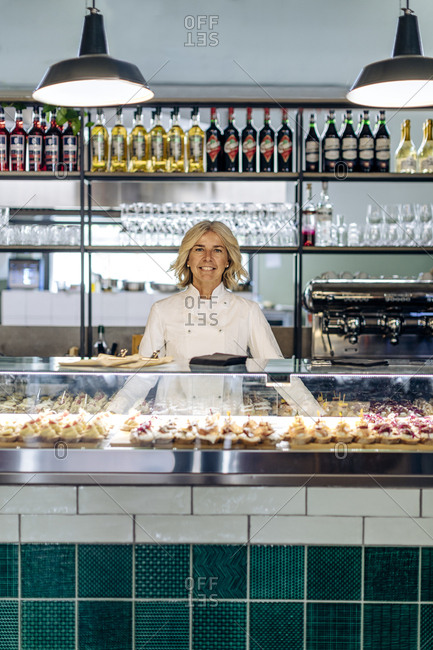 Proud bistro owner standing behind pastry counter