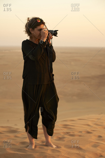 Woman taking a picture in the desert- Dune 7- Walvis Bay- Namibia