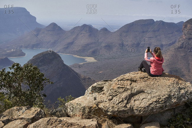 Woman taking a photo with her cell phone with a beautiful landscape background- Blyde River Canyon- South Africa