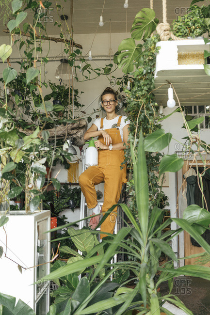 Portrait of a young woman standing on a ladder in a small gardening shop