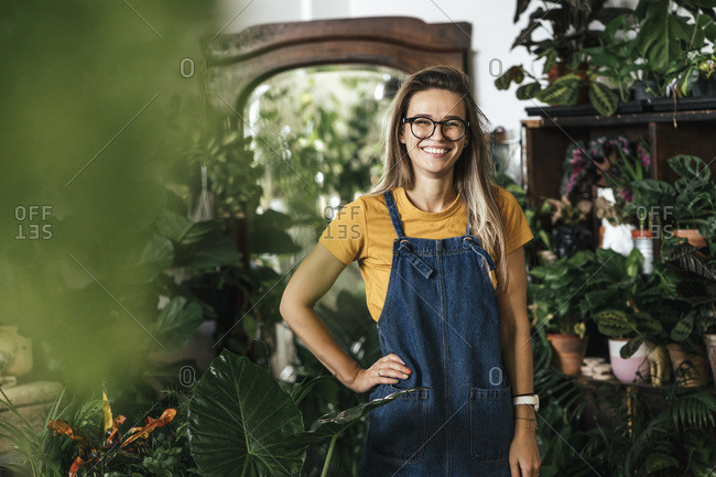 Portrait of a happy young woman in a small gardening shop