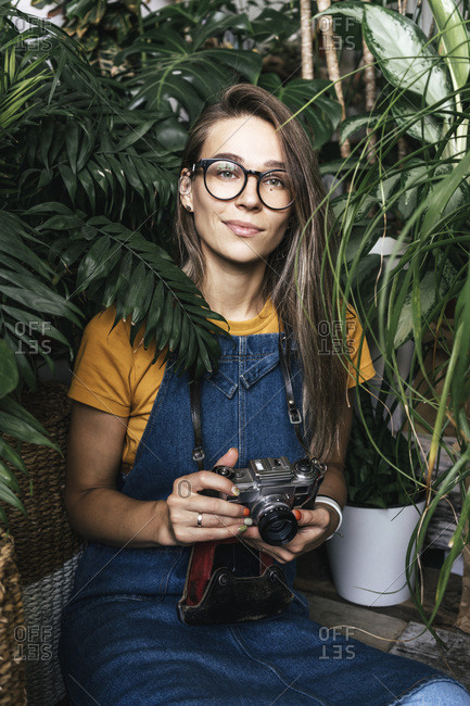 Portrait of a young woman with a camera in a small gardening shop