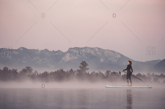 Woman stand up paddling on lake Kirchsee at morning mist- Bad Toelz- Bavaria- Germany