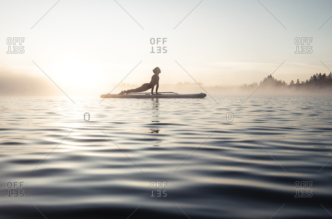 Woman practicing paddle board yoga on lake Kirchsee in the morning- Bad Toelz- Bavaria- Germany