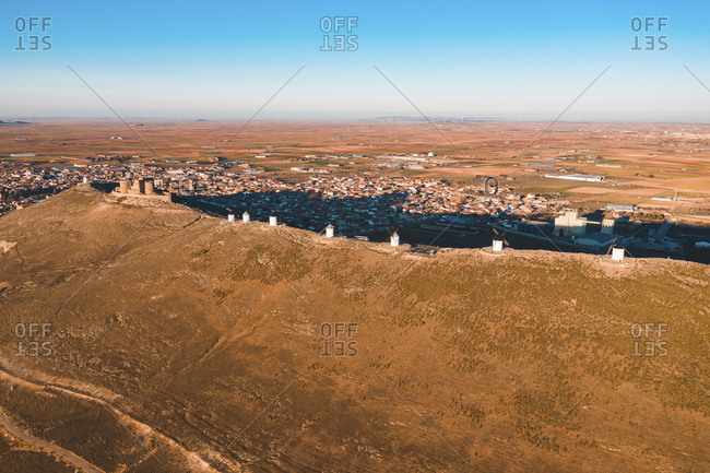 Spain- Province of Toledo- Consuegra- Row of old windmills standing on top of brown hill