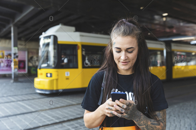 Portrait of tattooed young woman text messaging- Berlin- Germany