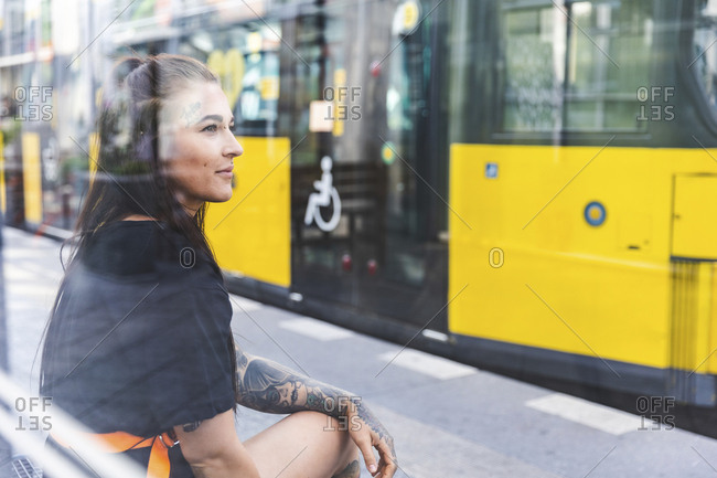 Portrait of tattooed young woman waiting at tram stop- Berlin- Germany