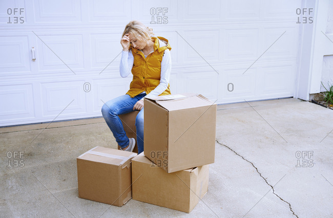 Tired woman sitting on cardboard boxes