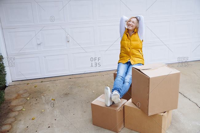 Happy woman sitting on delivered cardboard boxes