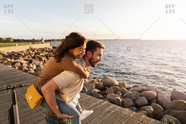 Man piggybacking happy girlfriend while enjoying on promenade by sea during vacation