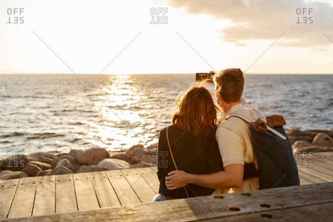 Rear view of couple taking selfie on smart phone while sitting against sea