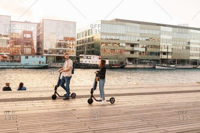 Full length of couple riding electric push scooters on promenade by river in city