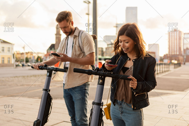 Male and female commuters scanning through mobile phone while unlocking electric push scooters in city
