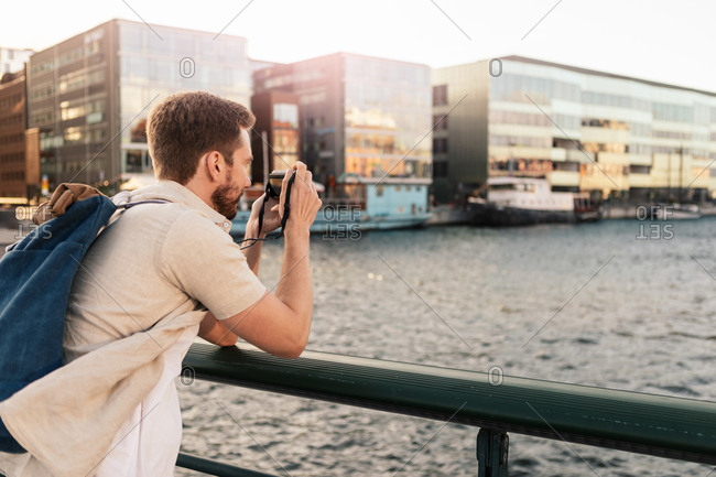 Man photographing river while standing by railing in city