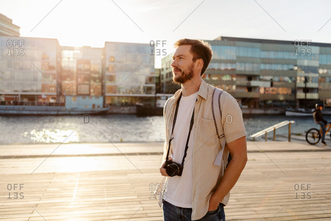 Thoughtful male tourist with camera standing on promenade in city