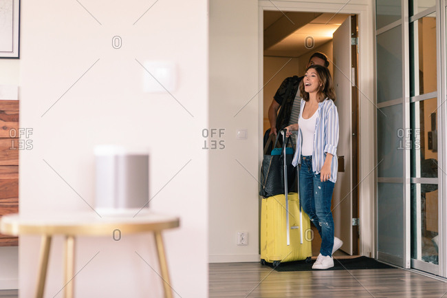 Excited couple with luggage entering in apartment during vacation