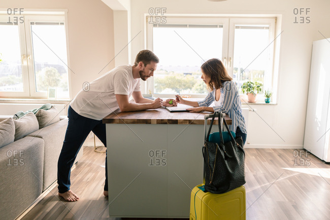 Man looking at woman filling form while standing with luggage in apartment during staycation