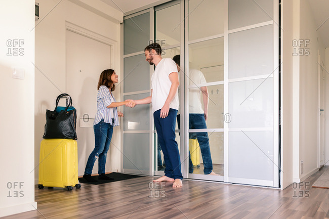Owner greeting woman with luggage while standing against door in apartment