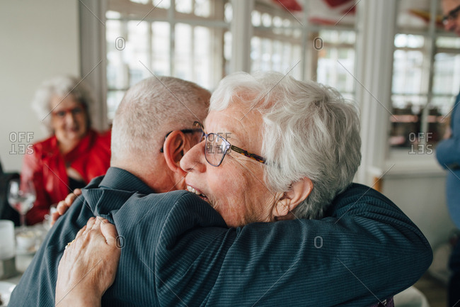 Senior man embracing woman while sitting in restaurant