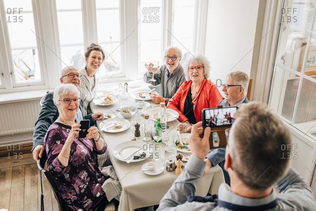 Waiter clicking photograph of Senior friends sitting in restaurant