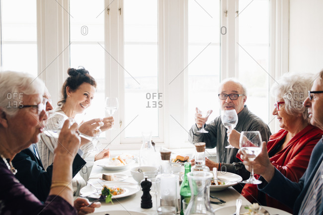 Senior friends with wineglass toasting in restaurant
