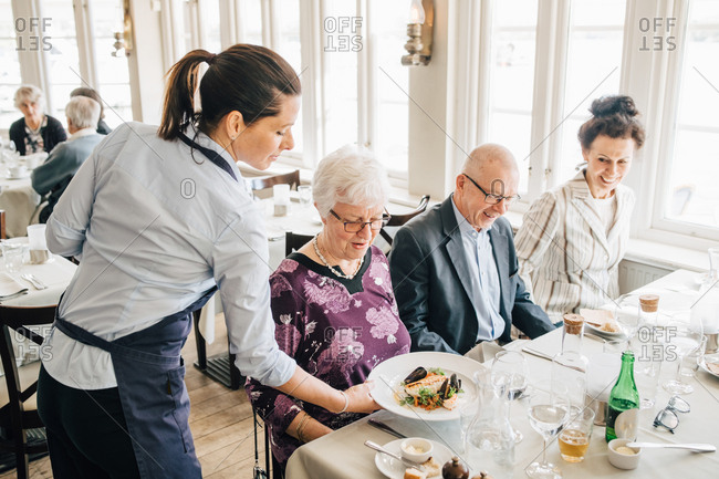 Owner serving food to senior friends sitting by restaurant table