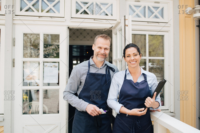 Male and female restaurant owners standing outdoors