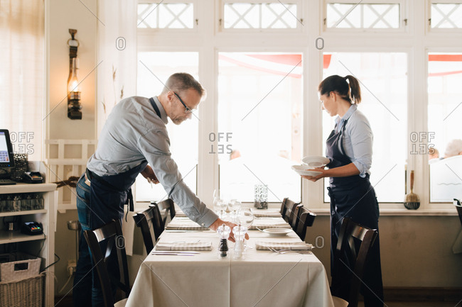 Male and female coworkers arranging table in restaurant