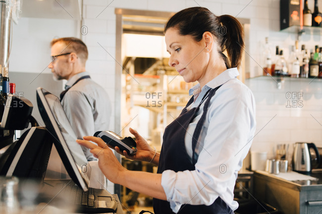 Owner using computer while holding credit card reader in restaurant