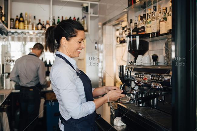 Smiling barista using coffee maker in restaurant