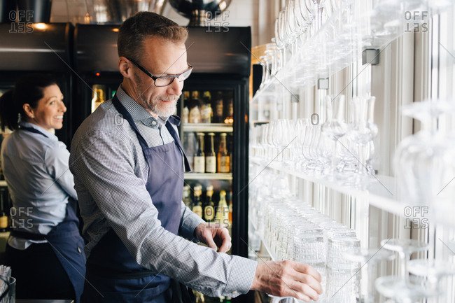 Mature man arranging wineglasses while waitress in background at restaurant